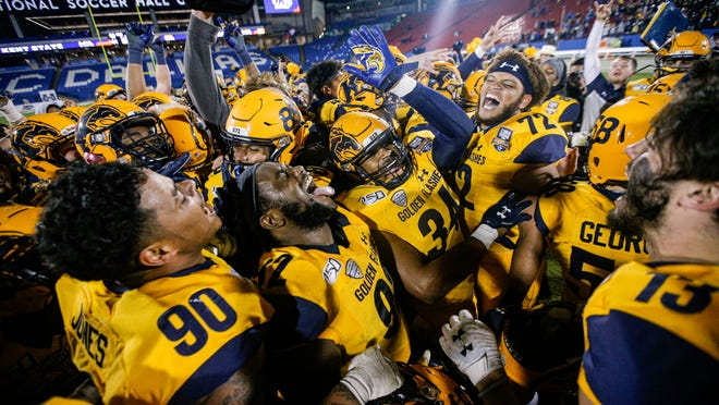 Kent State football players, pictured celebrating last December's Frisco Bowl victory over Utah State, could return to campus for voluntary workouts as soon as next week.