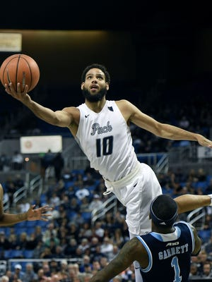 Nevada's Caleb Martin goes over Rhode's Jarvis Garrett to score in the second half of Monday's game at Lawlor Events Center.
