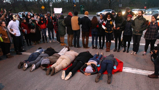Protesters lay across part of Wilson Boulevard during 4 and a half minutes of silence, as they gather to protest the decision in Ferguson, Missouri, to not charge police Officer Darren Wilson after he shot and killed Mike Brown.