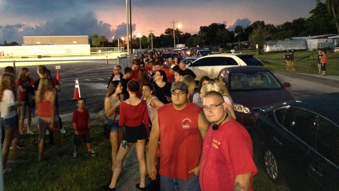 Fans and cars line up outside closed gates at North Fort Myers High School waiting out a lightning delay.