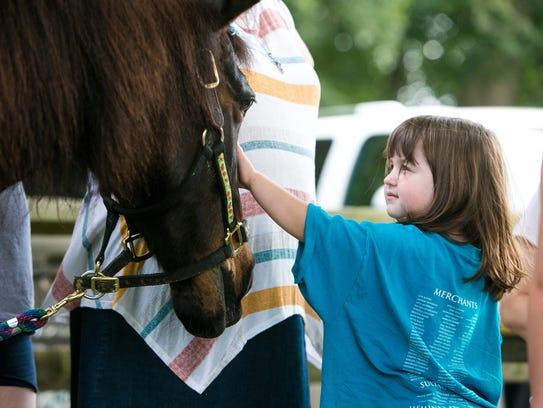 Eliza Heckscher, 4, pets Cutie as she joins other children
