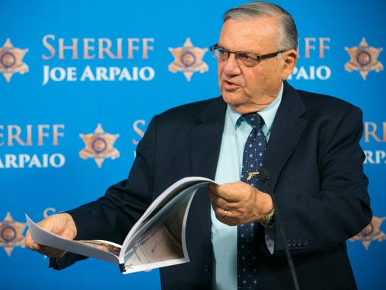 Then-Sheriff Joe Arpaio holds up photos of dogs found