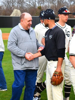 Jerry Caton and Lone Grove High School baseball coach Tyler Pybas shake after the ceremonial first pitch on Monday. Caton threw the first pitch after the field's dedication to his late brother and former Lone Grove baseball coach, Gene Caton.