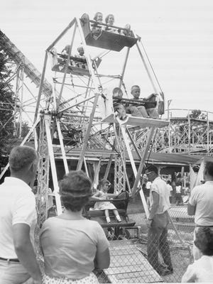 Parents watch their children enjoying a small Ferris wheel ride at Riverside Amusement Park in Indianapolis on Aug. 13, 1960. The park, located on West 30th Street at the White River, opened in 1903 and operated until the end of the 1970 season.