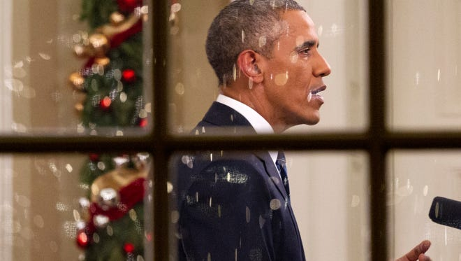 With Christmas lights reflected in the window, President Barack Obama makes an address to the nation in the Oval Office of the White House in Washington, Sunday, Dec. 6, 2015.