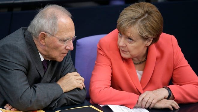 German Finance Minister Wolfgang Schaeuble, left, and Chancellor Angela Merkel, right, speak during a meeting of the German federal parliament, Bundestag, in Berlin, Germany, Thursday, June 18, 2015.