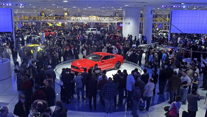 Auto enthusiast pack into Cobo Center to check out new Ford model cars including the 2015 Ford Mustang, center, during the first public day of the 2014 North American International Auto Show on  Jan. 18, 2014.