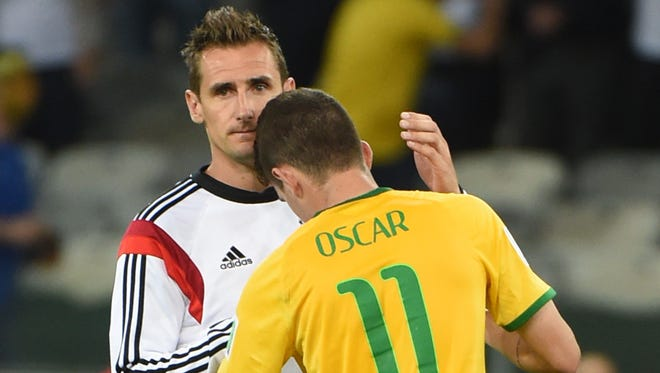 Forward Miroslav Klose of Germany comforts Brazil midfielder Oscar after their World Cup semifinal at The Mineirao Stadium in Belo Horizonte on Tuesday.