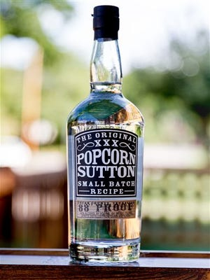 The new bottle and label design of Popcorn Sutton whiskey is displayed, Friday, Aug. 21, 2015 in Nashville, Tenn. The Newport, Tenn.-based brand, named after a legendary moonshiner, changed the bottling and label after being sued by the owner of Jack Daniel's for trademark infringement because its previous design bottle closely resembled the classic Jack Daniel's bottle. (AP Photo/Erik Schelzig)