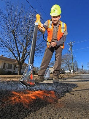 Jimmy Viger of the Anderson County Roads & Bridges Division works to patch a pothole on Fretwell Drive in this February file photo.