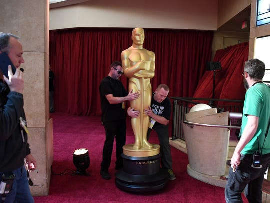 Workers set up an Oscars statue as preparations are