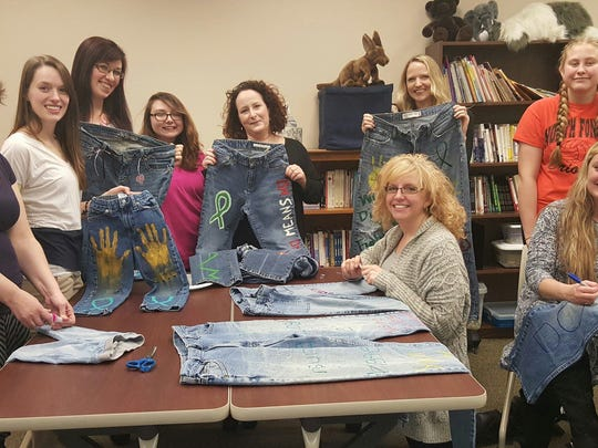 Jeans are decorated in advance of being hung on the Johnson Street bridge to promote sexual assault awareness.