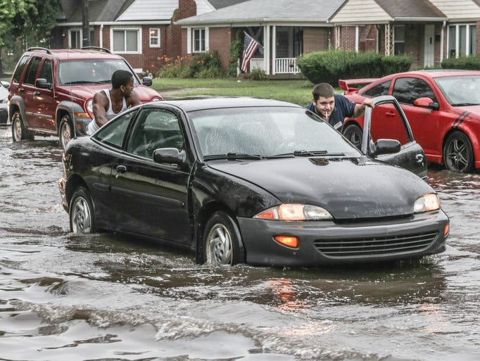 Wednesday July 23rd, 2014, Tony Davis, right, and C.J. Chaney, left, push a car out of flood waters near Keystone Ave. and Kessler Blvd., after a morning of storms and heavy rain in Indianapolis.