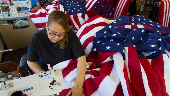 Maria Esperanza sews flags May 25, 2016, at Eder Flag Manufacturing Co. in Oak Creek, Wis.