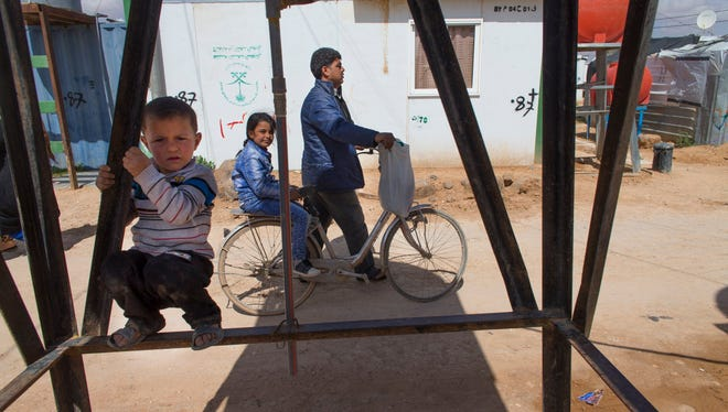 Mahmood Al Mekdad gets on his bike to take his 8-year-old daughter, Sandy, back to their home at the Zaatari refuge camp in Jordan, about 15 miles from the Syrian border.  Sandy has a congenital defect known as tethered spinal cord that limits the movement of the spinal cord within the spinal column. On Sept. 21, Sandy had surgery at the University of Jordan.