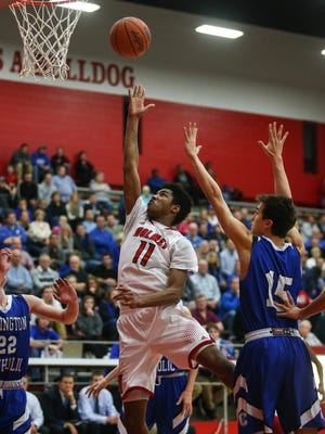 Holmes' Jaiden Greene puts up a layup Friday night as Covington Catholic's Andy Flood tries to defend.