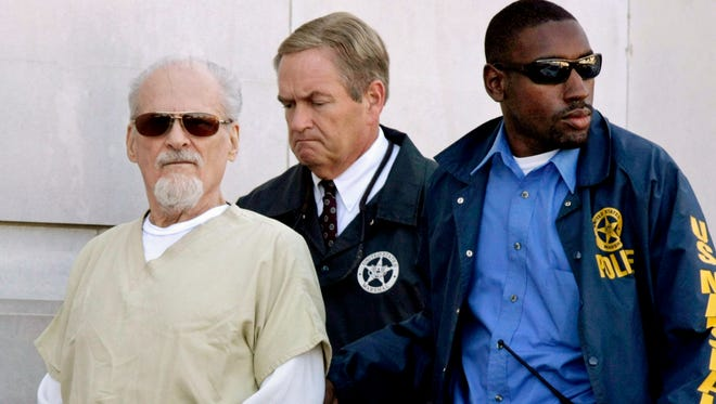 FILE - In this July 23, 2009, file photo, Tony Alamo, left, is escorted to a waiting police car outside the federal courthouse in Texarkana, Ark. Alamo died in prison Tuesday, May 2, 2017.