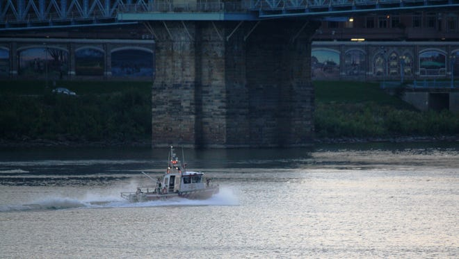 A rescue boat searches the Ohio River after two people on a tour bus called 911 and reported seeing a body in the river Monday night.