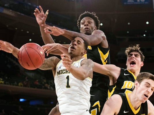 Iowa forward Tyler Cook, second from left, forward Luka Garza, second from right, and forward Nicholas Baer, right, stop Michigan guard Charles Matthews (1) from scoring a basket during the first half of an NCAA college basketball game in the second round of the Big Ten conference tournament, Thursday, March 1, 2018, at Madison Square Garden in New York. (AP Photo/Mary Altaffer)