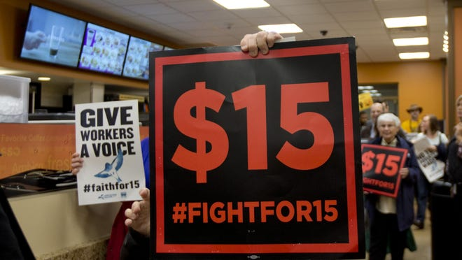 Supporters of a $15 minimum wage walk through a Dunkin' Donuts store during a rally at the Capitol on Nov. 10 in Albany.