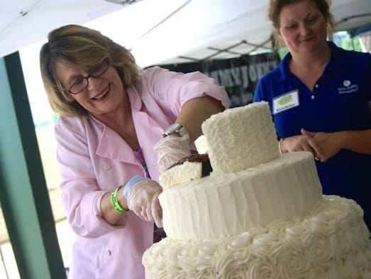 Jeannette Hillman, owner of Classy Cakes, cuts a piece of cake during the seventh annual Taste of Gallatin held Thursday, June 5 at Triple Creek Park.