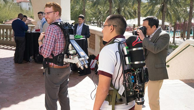 Robert Gregg, left, a professor at the University of Texas at Dallas, tries a jetpack, assisted by demonstrator Eduardo Fernandez, who is wearing a personal cooling device, at the Wearable Robotics Association's WearRAcon16 in Phoenix on Feb. 10.