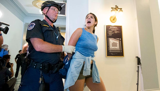 Samantha Coronado, a LUCHA Arizona organizer, is led away by a U.S. Capitol Police officer after her arrest during a protest over the Senate health care bill outside Sen. Jeff Flake's office.