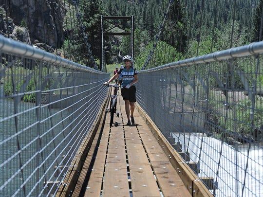 Phillips walks her bike across a bridge over the Truckee River on June 11, 2013.