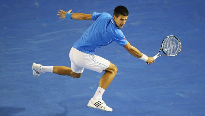 Novak Djokovic of Serbia stretches for a backhand in his quarterfinal match against Milos Raonic of Canada.