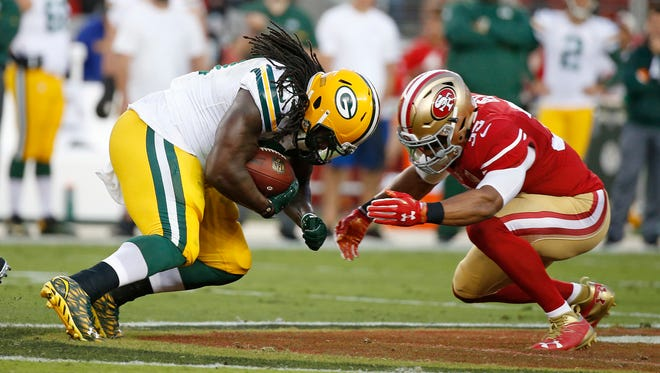Green Bay Packers running back Eddie Lacy is stopped by San Francisco 49ers free safety Eric Reid.