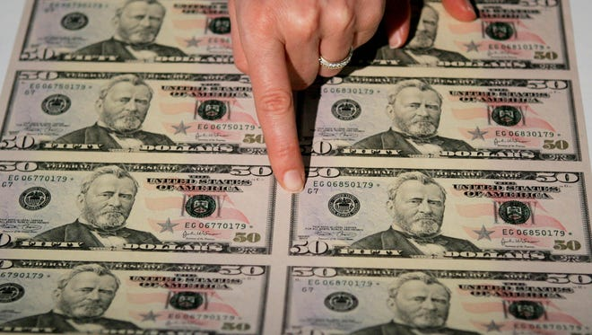 "WASHINGTON - SEPTEMBER 28:  Julie Borchard of the U.S. Treasury Department points out new improvements on the newly unveiled fifity dollar bill September 28, 2004 in Washington, DC. The newly redesigned bill, with a ""Stars and Stripes"" design theme, was released into circulation today.  (Photo by Mark Wilson/Getty Images)"