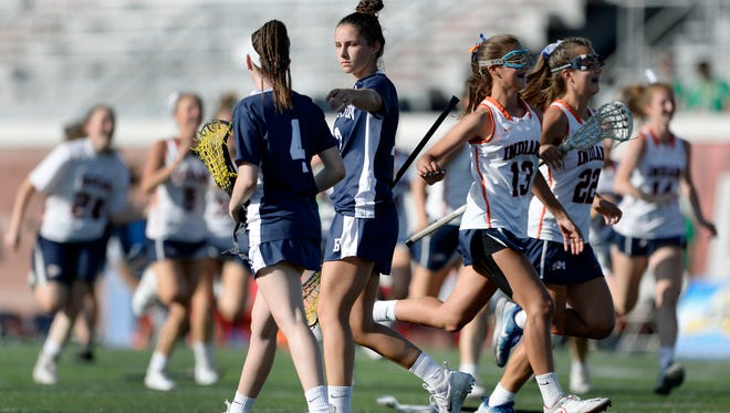 Brighton's Caroline Lederman, right, and Katie Smolensky walk off the field as Manhasset players celebrate their win Saturday in the Class B final at the NYSPHSAA Girls Lacrosse Championships in Cortland. Brighton's season ended with a 6-4 loss to Manhasset-VIII in the championship game.