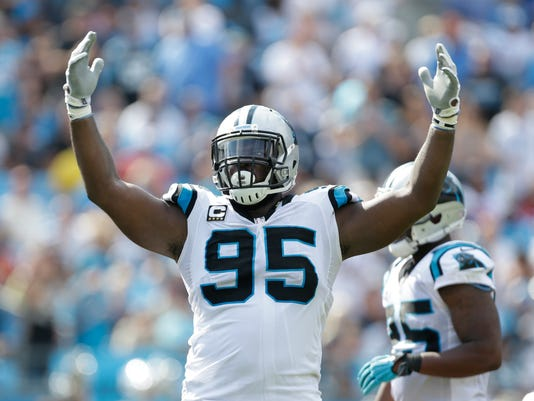 FILE - In this Sept. 20, 2015, file photo, Carolina Panthers' Charles Johnson (95) fires up the crowd during the second half of an NFL football game against the Houston Texans in Charlotte, N.C. Defensive end Charles Johnson has agreed to take a major pay cut to return to the Carolina Panthers. The Panthers announced Wednesday, March 9, 2016,  the nine-year NFL veteran has re-signed with the team after being released last week in a salary cap move. (AP Photo/Bob Leverone, File)