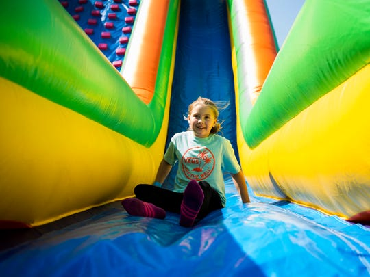 Ellie Ross, 11, slides down an inflatable at Riverfest