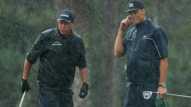 Phil Mickelson, left, and Tom Brady of the Tampa Bay Buccaneers react on the 13th green in the rain during The Match: Champions for Charity golf round on May 24. The duo lost to Tiger Woods and Peyton Manning.