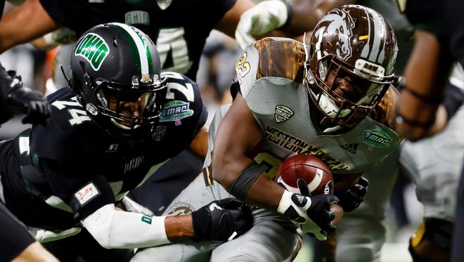 Western Michigan Broncos running back Jamauri Bogan (32) is tackled by Ohio Bobcats safety Toran Davis (24) in the first half of the 2016 Mid-American Conference Championship Game at Ford Field.