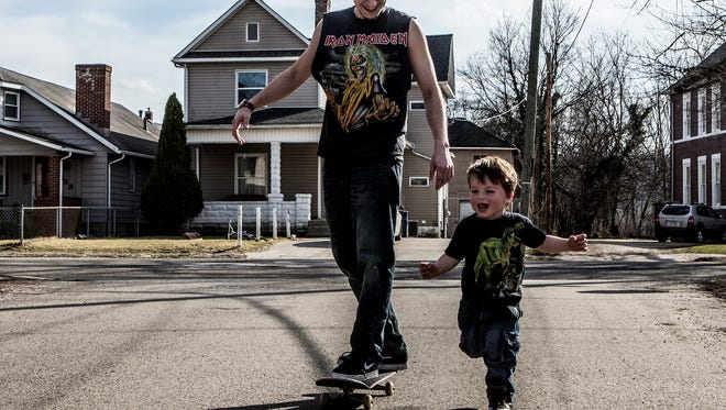 Jacob Montgomery laughs as his girlfriend's son, Shonathin races him while he rides his skateboard in front of his house. The pair were enjoying the unseasonable nice weather Tuesday.