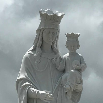 A marble statue of the Virgin Mary is the focal point