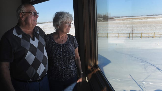 Duane and Marilyn Schreurs look out of the window of their home near Baltic. Schreurs surprised 10 area churches with donations of $25,000 each.
