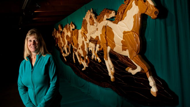 """Kathy Wise, of Emmett, stands next to her 23-foot long by 6-foot high intarsia wood piece called, """"Wild Horses."""" It will be displayed at ArtPrize."""