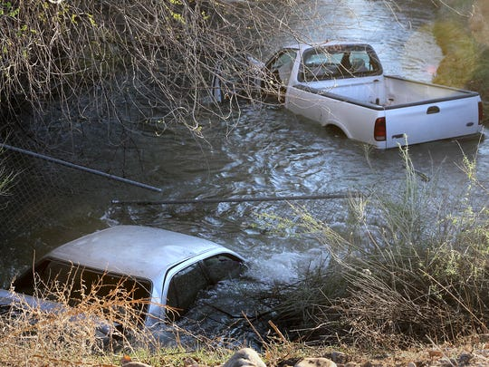 Two vehicles sit in Willett Ditch just off East Broadway Avenue near the south side of the Animas River in Farmington on Saturday. One man has been arrested on suspicion of drunken driving in connection to the wreck.