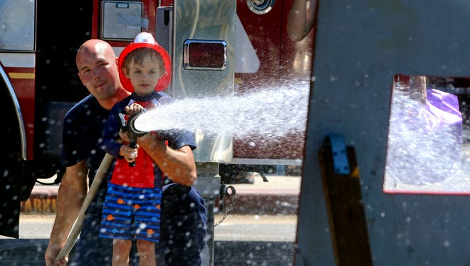 Nathan Usategui of the Pensacola Fire Academy helps Noah Jacobi man a fire hose during a previous Firefighters Challenge. This year's event is Friday and Saturday at Pensacola Beach.