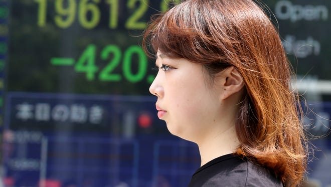 A woman walks past an electronic stock board of a securities firm in Tokyo, Friday, Aug. 21, 2015.