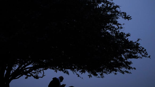A man looks at his phone while sitting in a park at twilight in Kansas City, Missouri.
