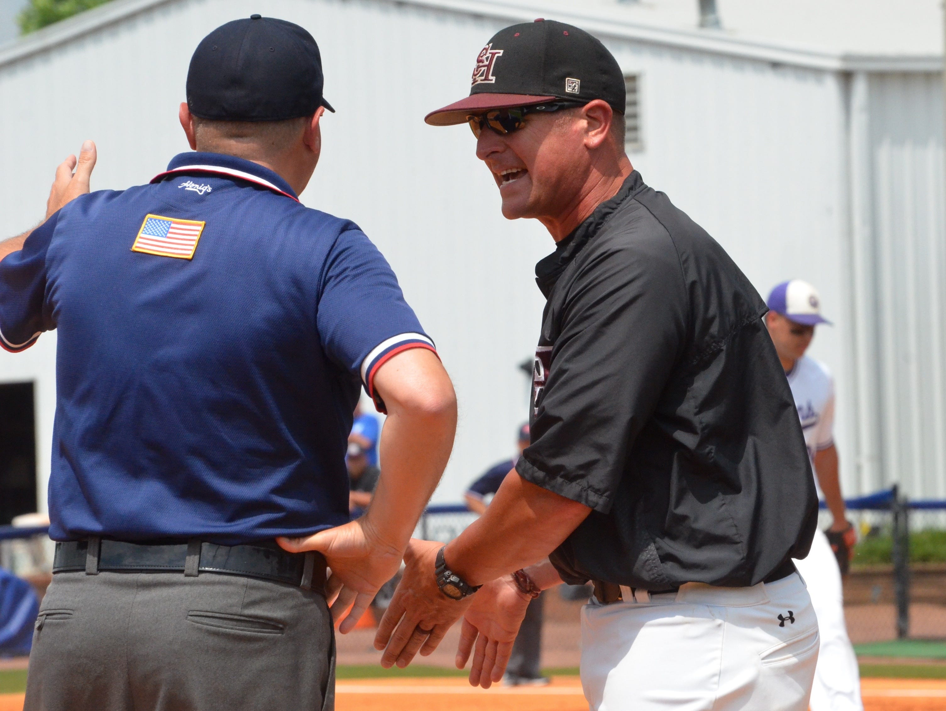 Spring Hill coach Paul Lamm talks to the third base umpire during Friday's TSSAA Class AA state baseball championship game at MTSU's Reese Smith Jr. Field.