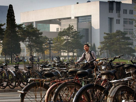 """Bicycles are the most popular way to get around campus at Tsinghua University in Beijing. Tsinghua, founded in 1911, has a motto: """"To act is better than to speak."""" At Tsinghua, considered by some as the Chinese equivalent of the prestigious Massachusetts Institute of Technology, 100% of graduates are placed in jobs. Other top Chinese schools boast similar placement rates."""