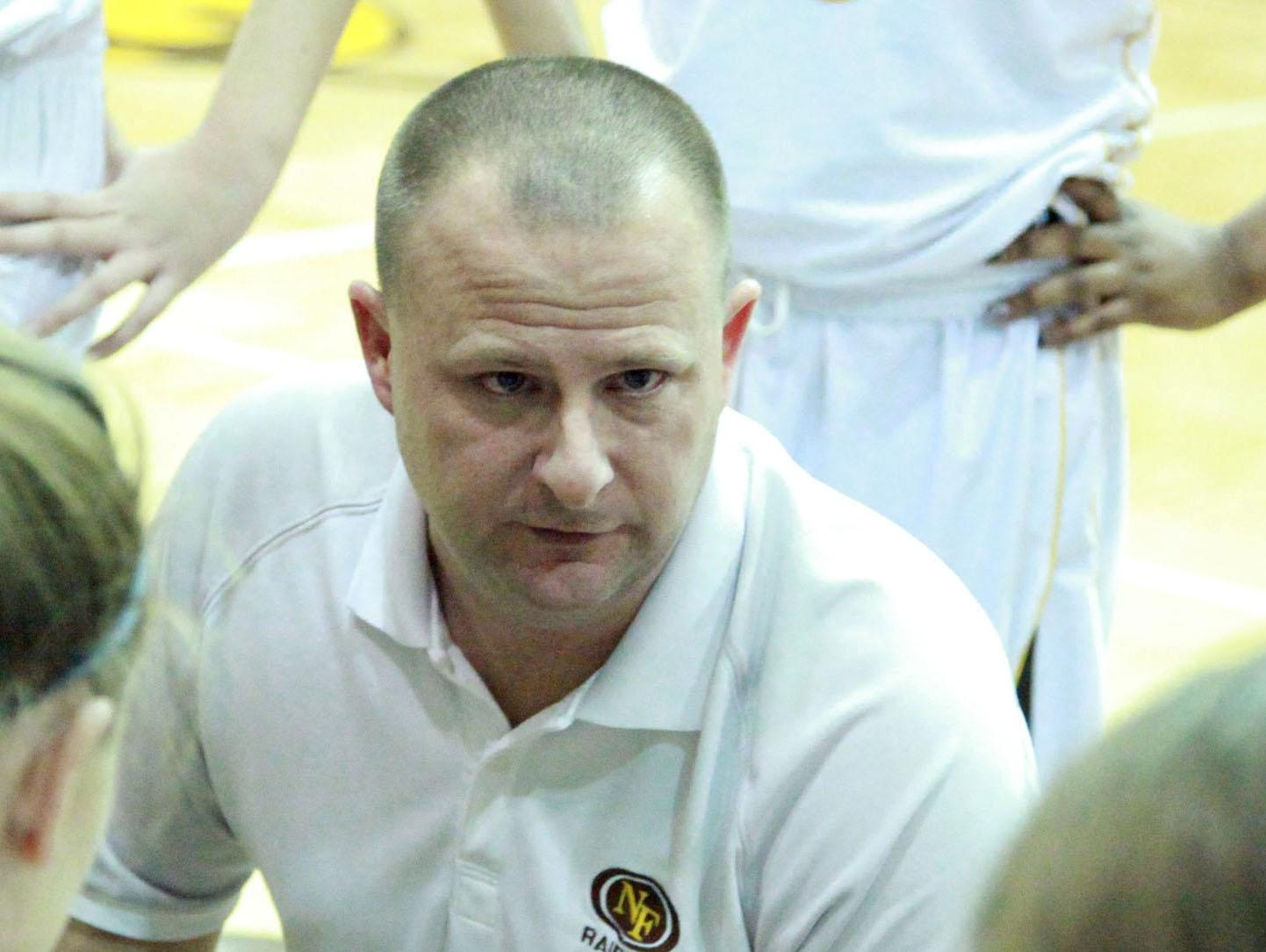 Coach Jeff Simpson gives instruction to his North Farmington team during a timeout.