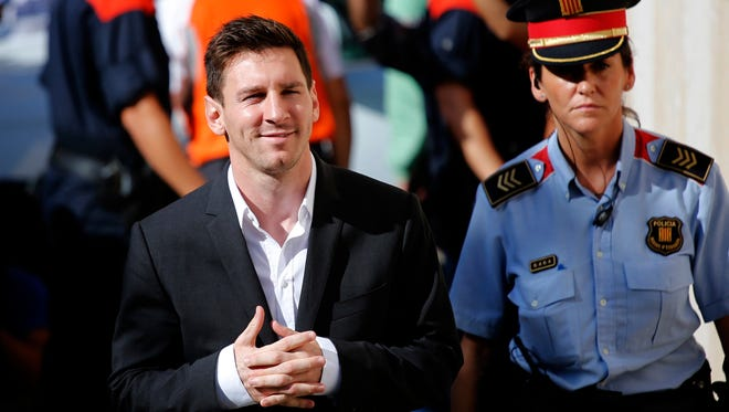 FC Barcelona star Lionel Messi, left, arrives at a court to answer questions in a tax fraud case in Gava, near Barcelona, Spain.