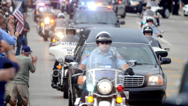 A hearse carrying Lt. Charles Joseph Gliniewicz passes through in Antioch, Ill., on Sept. 7, 2015.