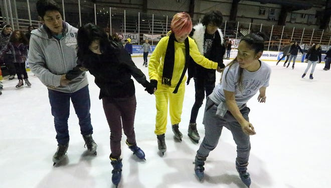 Rosie Gonzalez, right, shows her friends how to propel themselves over the ice Saturday at the El Paso County Events Center adjacent to the County Coliseum.